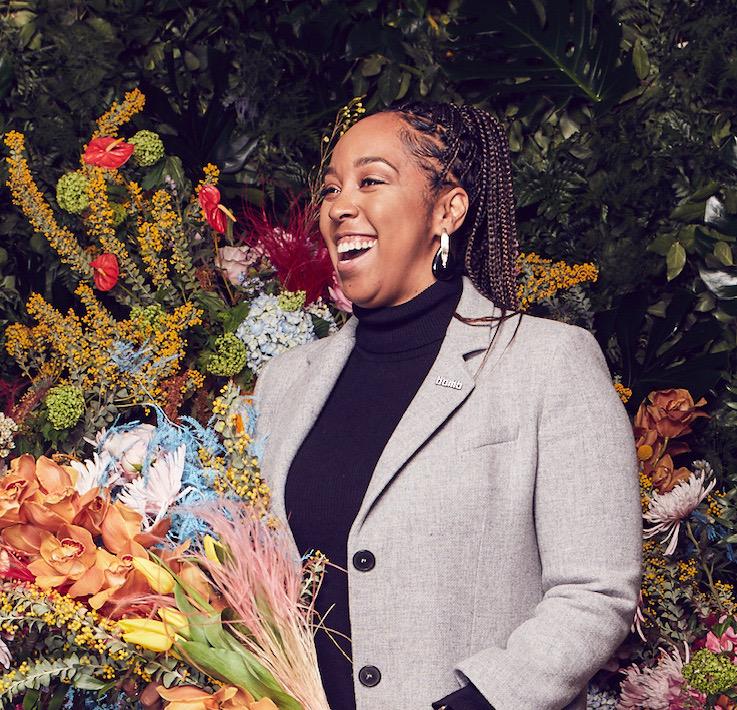 Joyous Black woman entrepreneur with flowers.